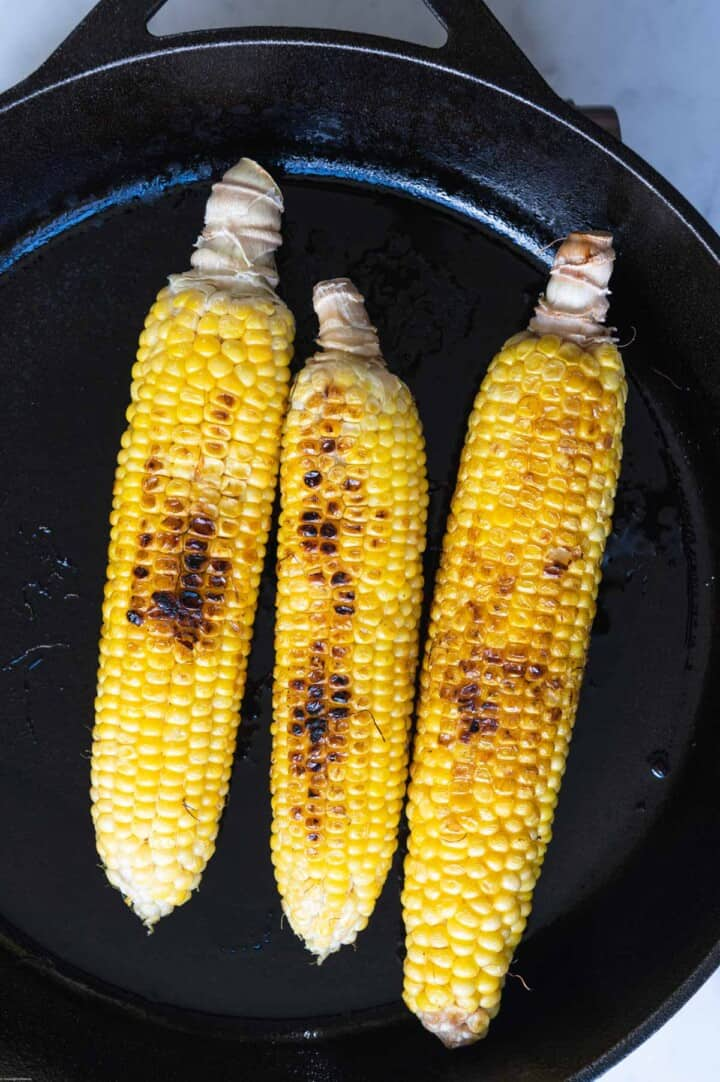 Three ears of charred corn in a skillet.