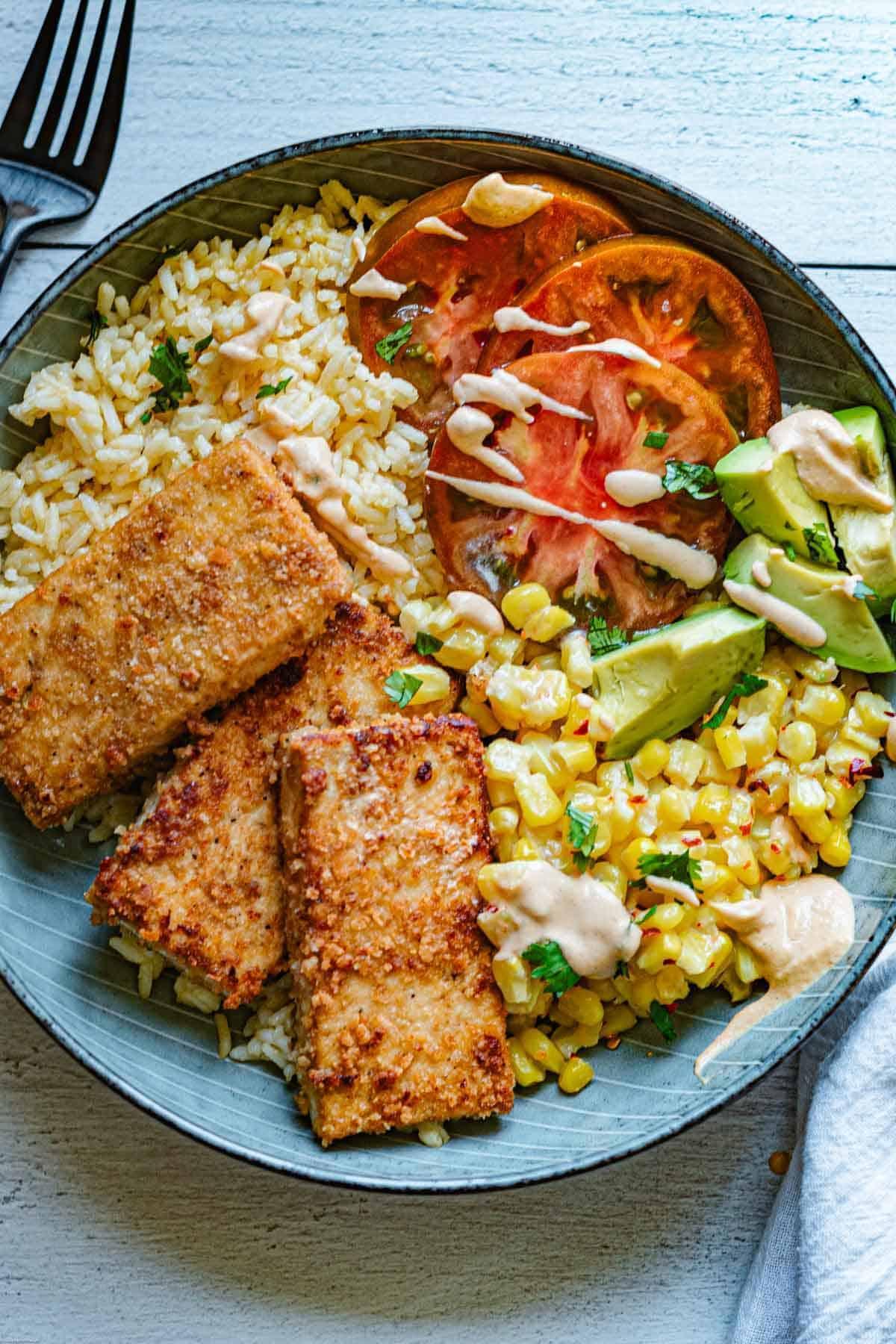 Crispy Tofu Bowl, Chipotle-Tahini, creamy sweet corn kernels, avocado, tomatoes, rice, and cilantro.