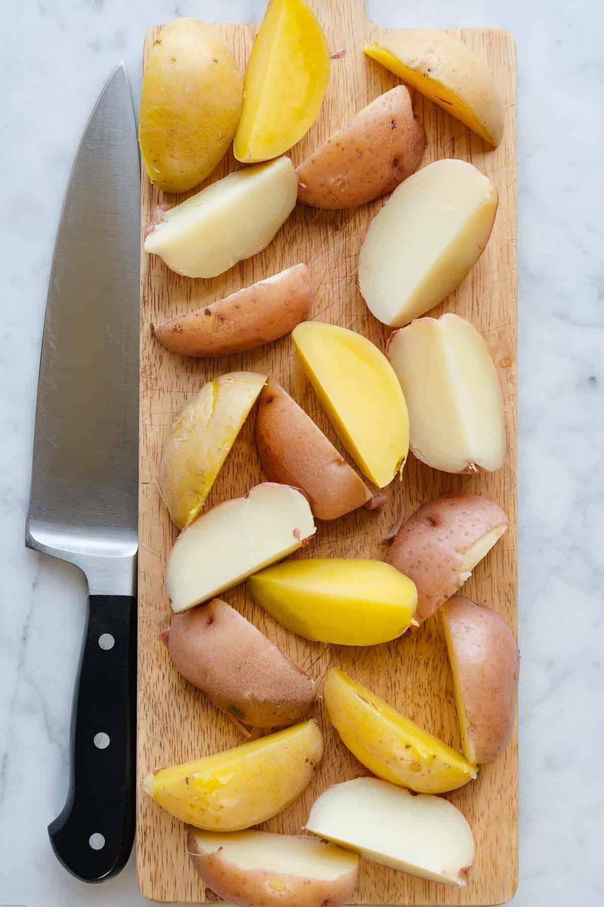 Sliced Yukon Gold potatoes on a cutting board.
