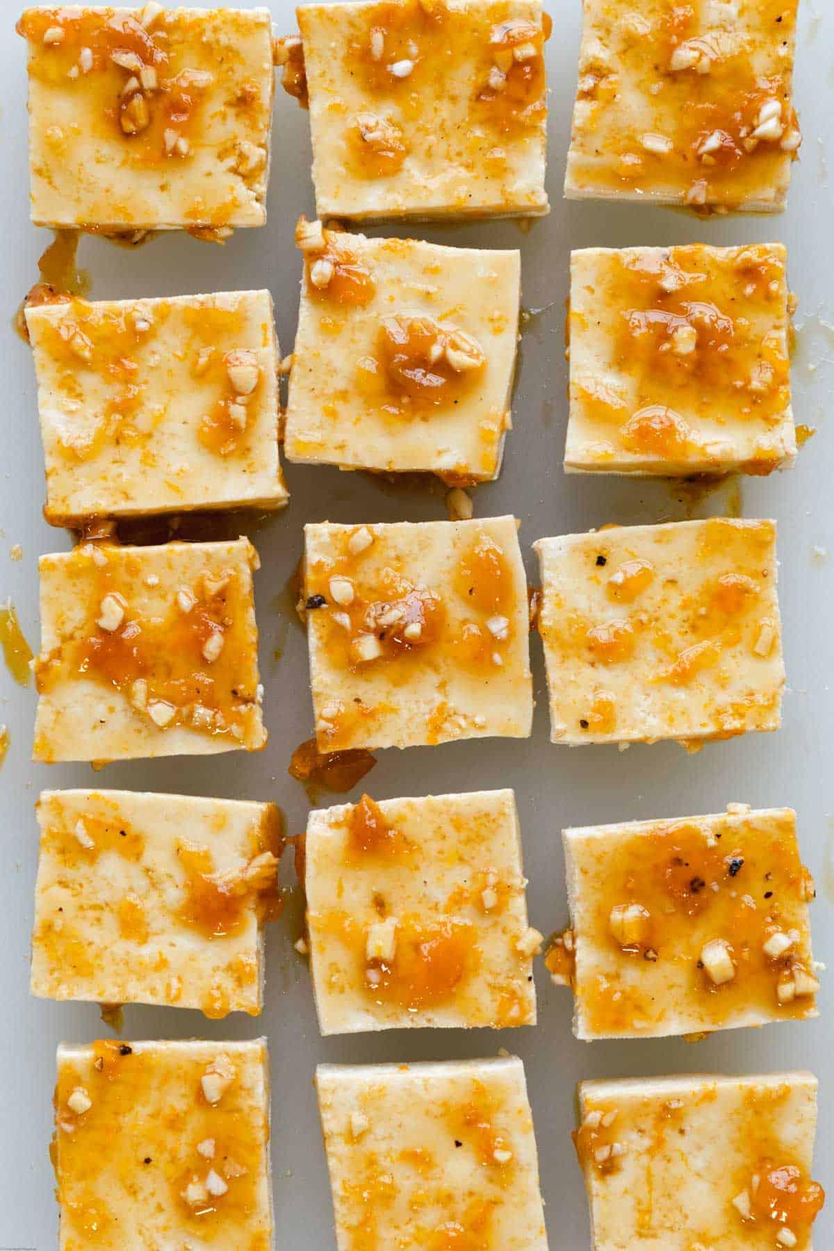 Tofu squares brushed with orange glaze and ready to bake.