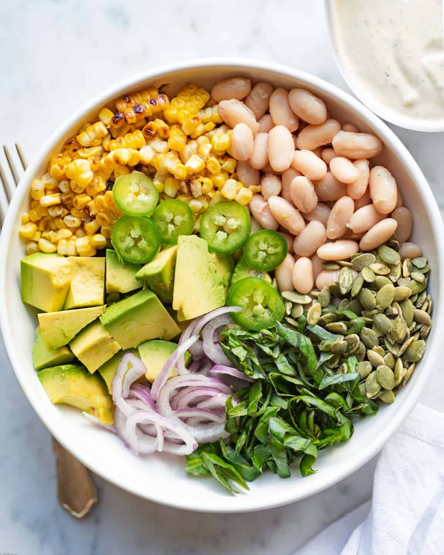 Corn kernels, white beans, pepitas, avocado, shallot, jalapeno, chopped basil, and creamy lemon pepper dressing for High-Protein Bean & Corn Salad.