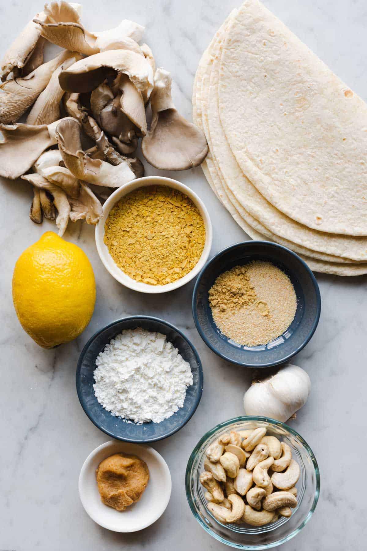 Ingredients for making Easy Cheesy Vegan Quesadillas:: Tortillas, oyster mushrooms, nutritional yeast, lemon, cornstarch, onion powder, garlic powder, ground mustard seed, mellow miso, garlic, and cashews.