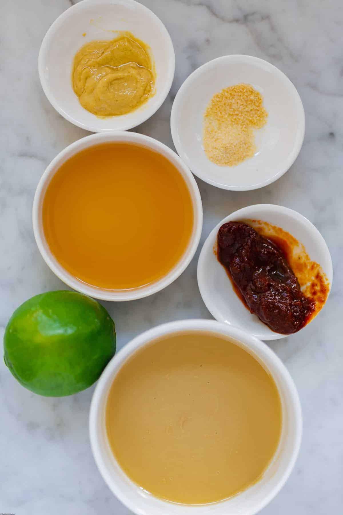 Dijon, onion powder, garlic powder, apple cider vinegar, chipotle in adobo sauce, lime, and tahini for making chipotle-tahini dressing.