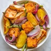 Orange-glazed tofu with roasted veggies in a white bowl for serving.