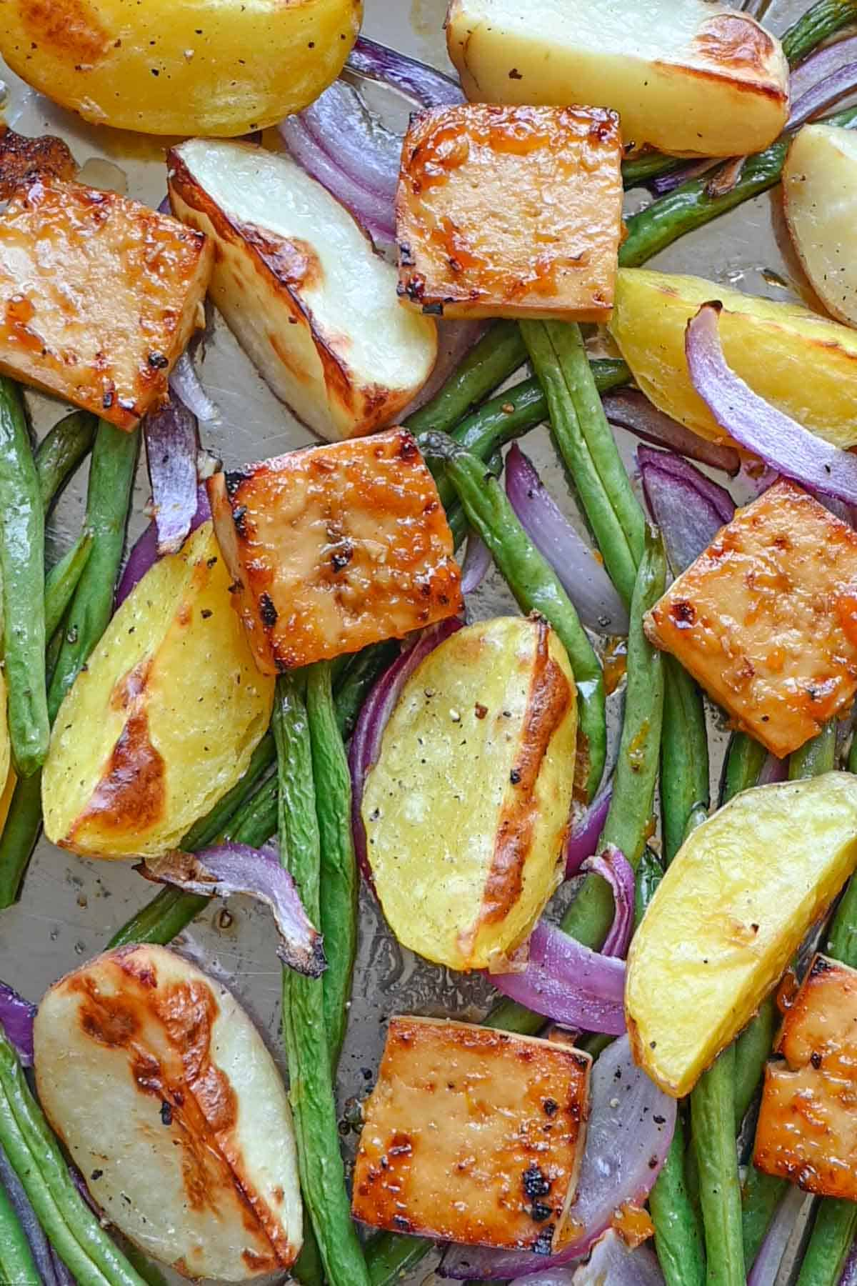 Crispy red onion, potatoes, green beans & protein on a large baking sheet.