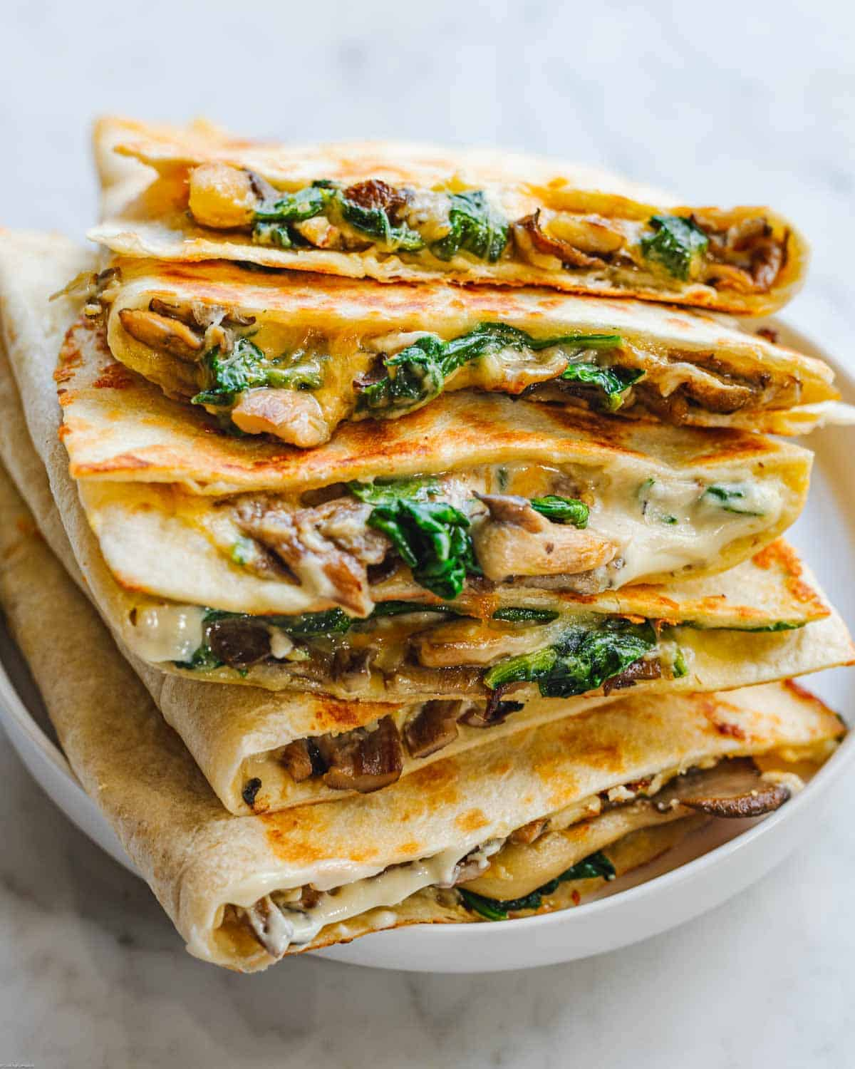 Stacked quesadillas filled with vegan cheese, mushrooms and spinach.