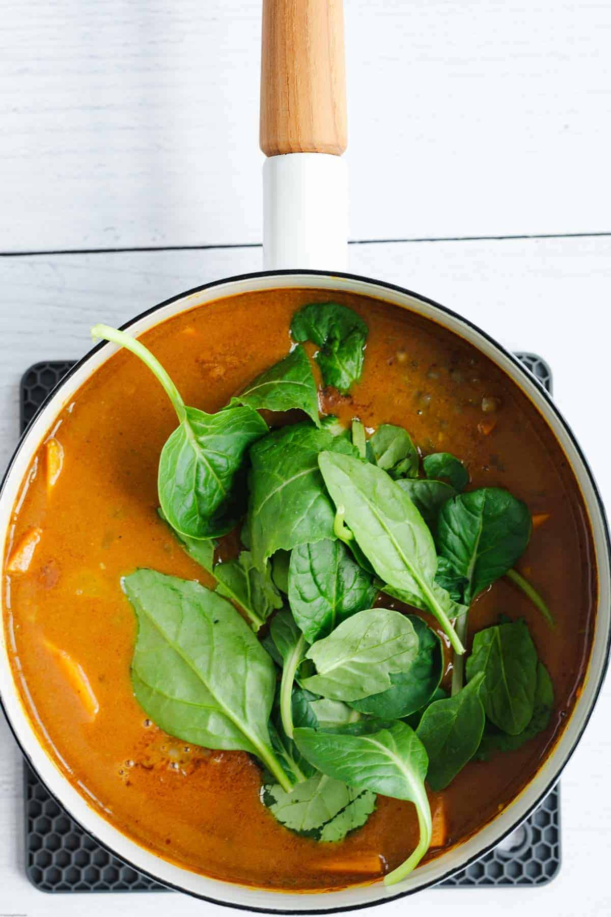 Adding the baby spinach to the curry.