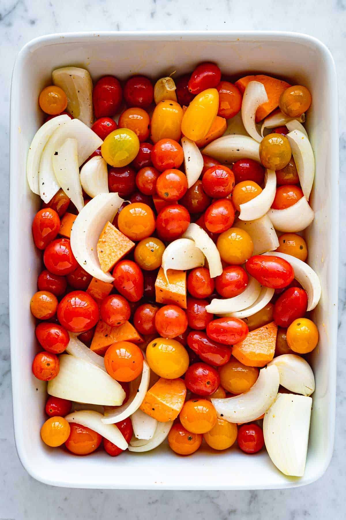 Cherry tomatoes, yellow onion wedges, chopped sweet potato, and garlic cloves tossed with olive oil in a baking dish.
