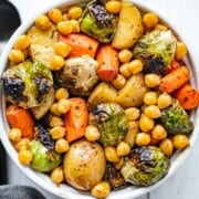 Roasted carrots, potatoes, Brussels sprouts, and chickpeas in a white bowl for serving.