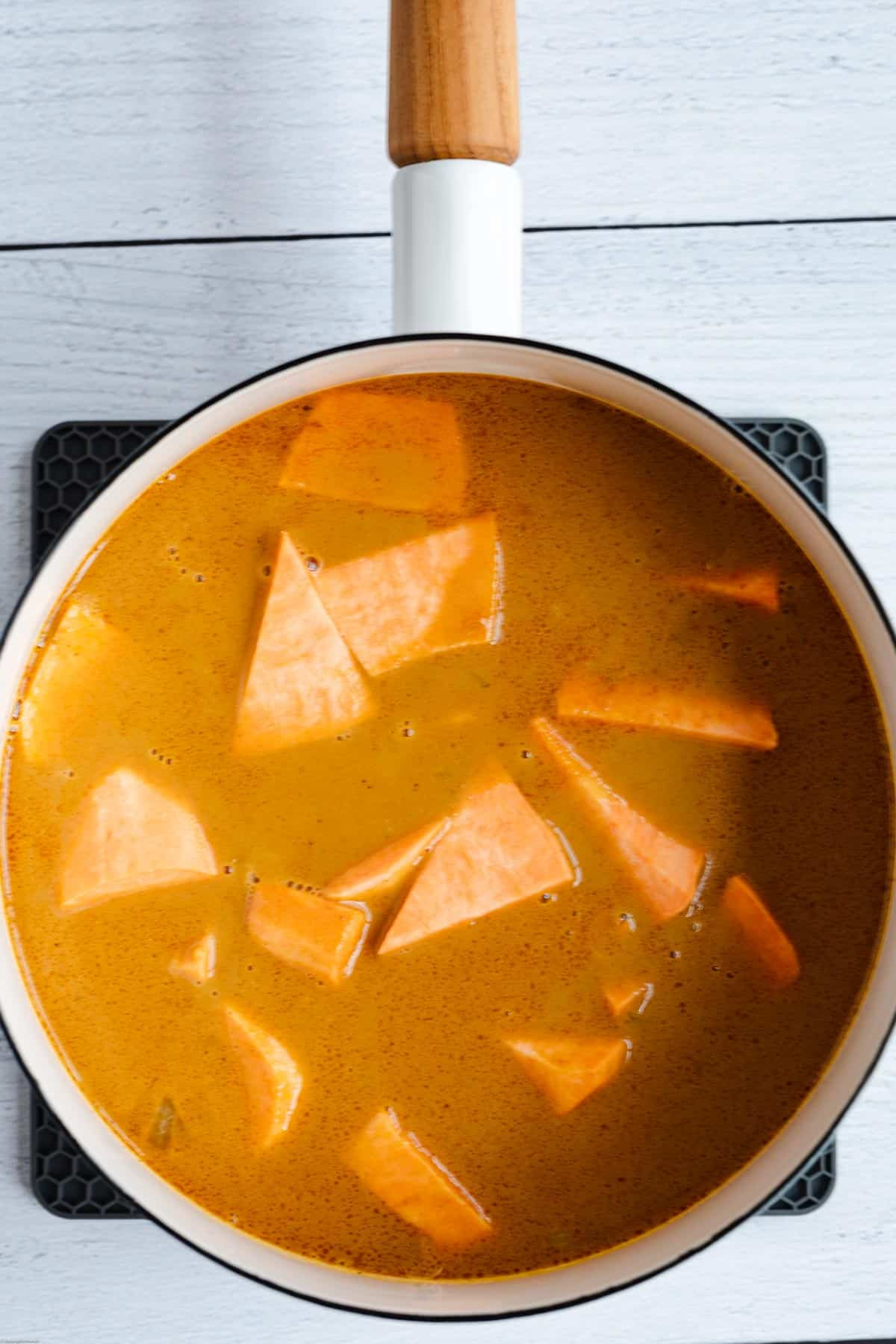 Adding sweet potato to the curry.