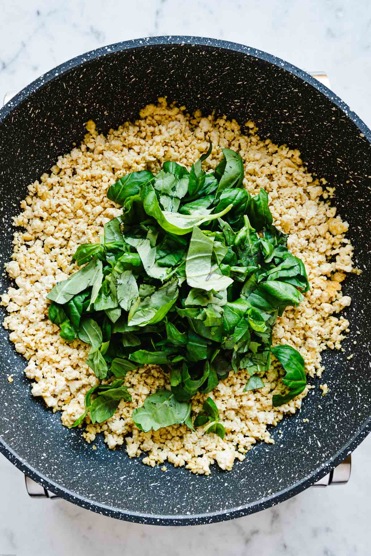Crumbled tofu with basil in a skillet.