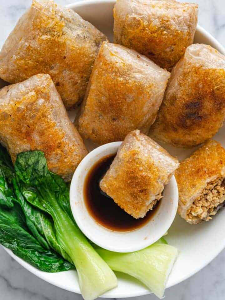 Easy Vegan No-Chop Dumplings with dipping sauce, and bok choy in a bowl.