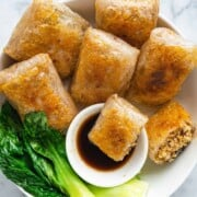 Easy Vegan No-Chop Dumplings with a dipping sauce, and bok choy in a bowl.