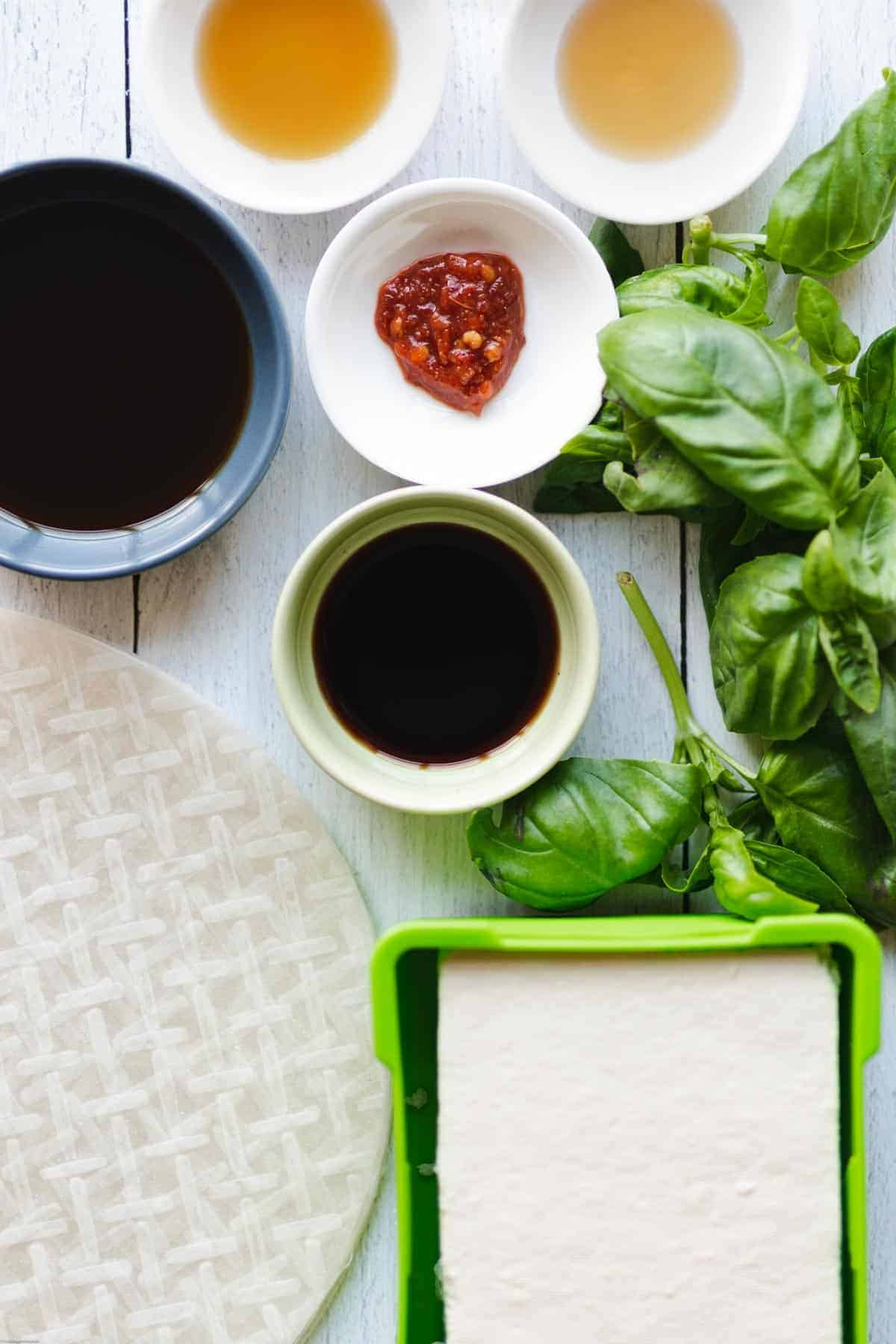 Ingredients for Easy Vegan No-Chop Dumplings: Rice paper, tofu, basil, sesame oil, ground ginger, coconut aminos, soy sauce, maple syrup, and chili garlic sauce.