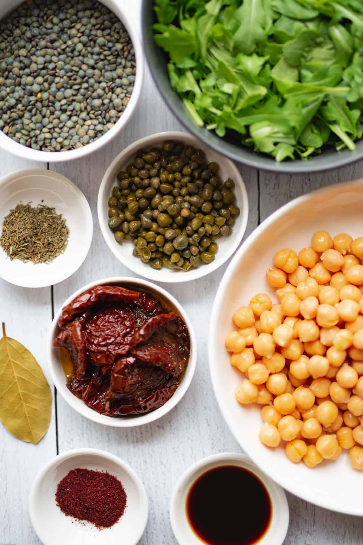 Ingredients for Chickpea Lentil & Sun-Dried Tomato Sumac Salad: chickpeas, lentils, arugula, tamari, capers, sun-dried tomatoes, dried thyme, bay leaf, and sumac.