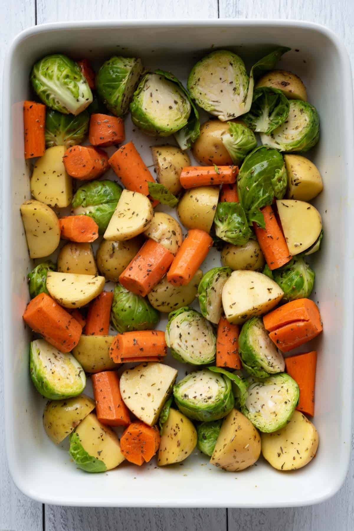 Roasted Brussels sprouts, carrots, and potatoes in a white casserole dish.