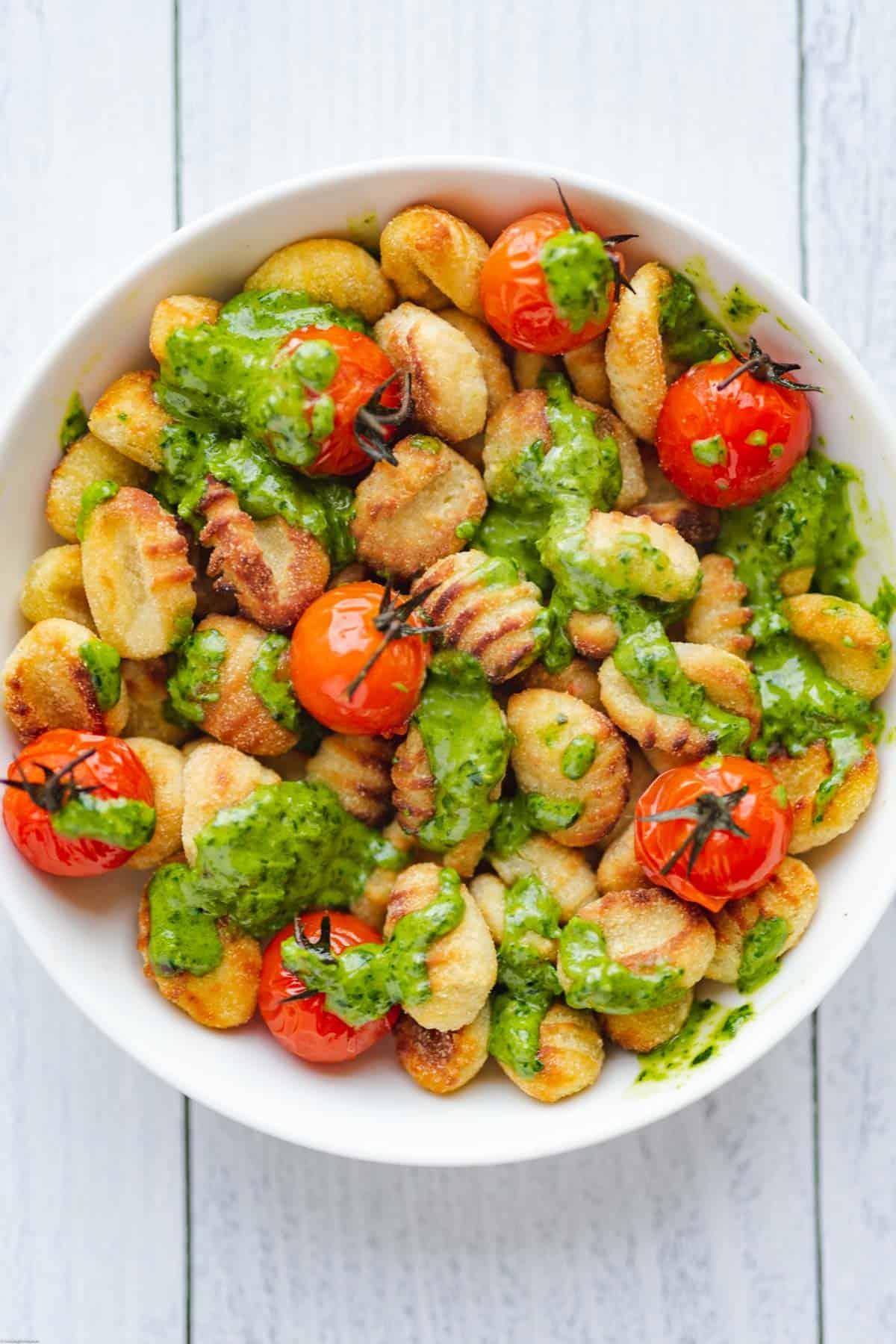 Pesto-Gnocchi & Burst Tomatoes in a white bowl.