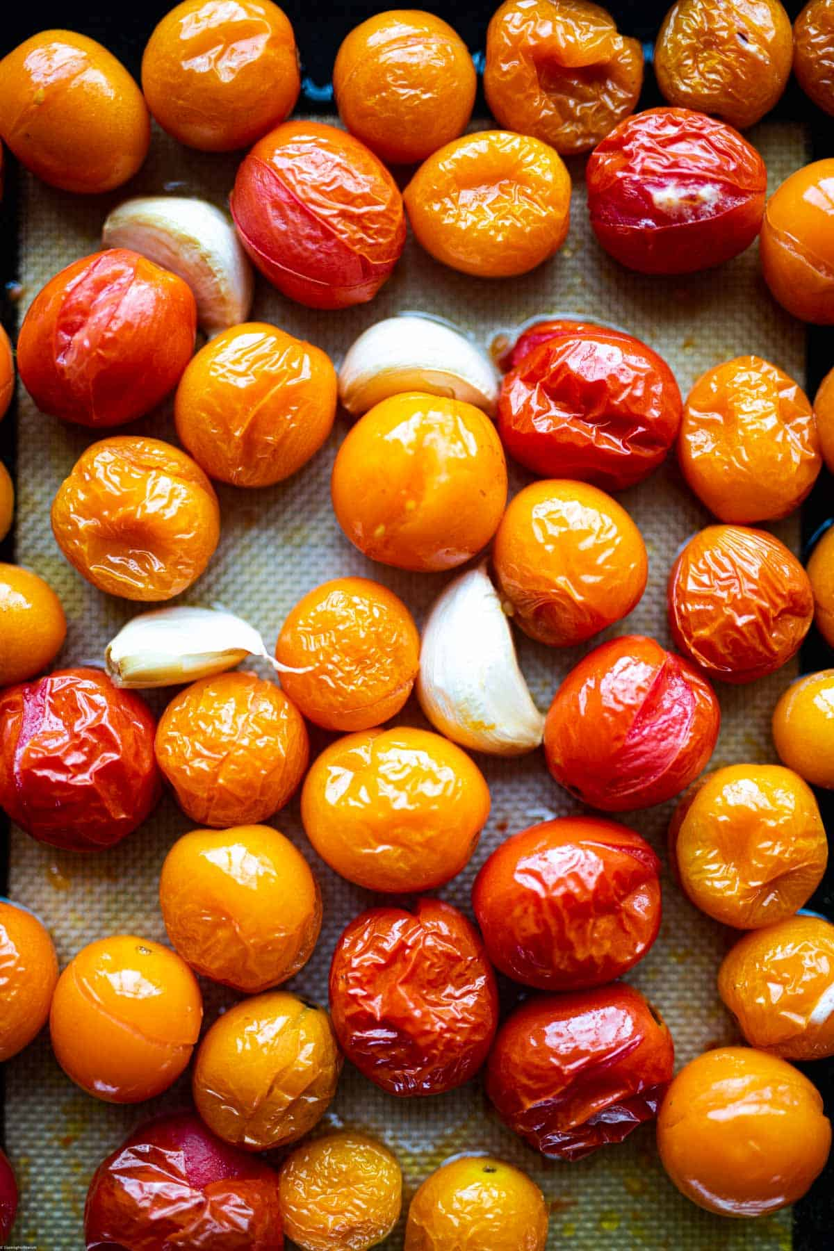 Burst cherry tomatoes on a baking sheet.