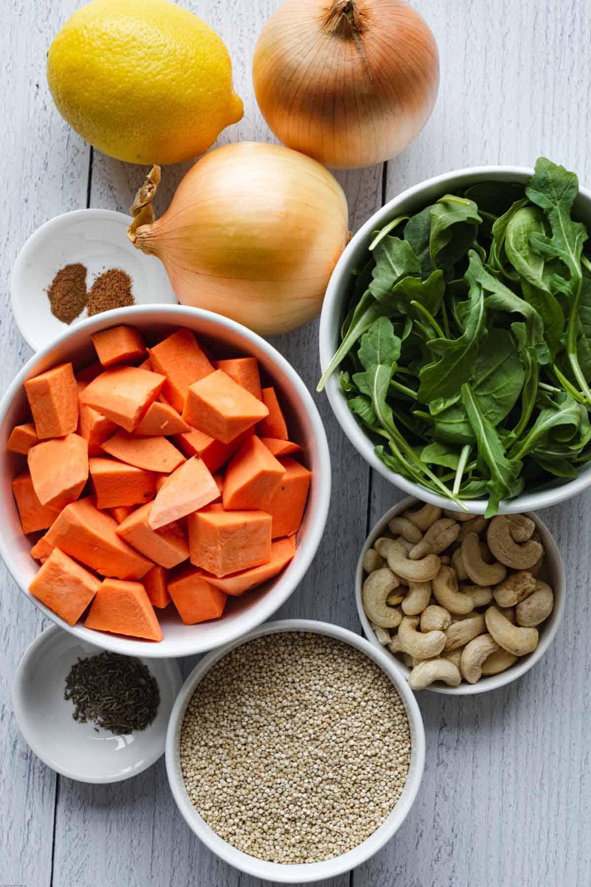 Ingredients for making Sweet Potato & Quinoa Salad with Tahini: onions, lemon, quinoa, cashews, dried thyme, ground cinnamon, ground nutmeg, sweet potato, and arugula.