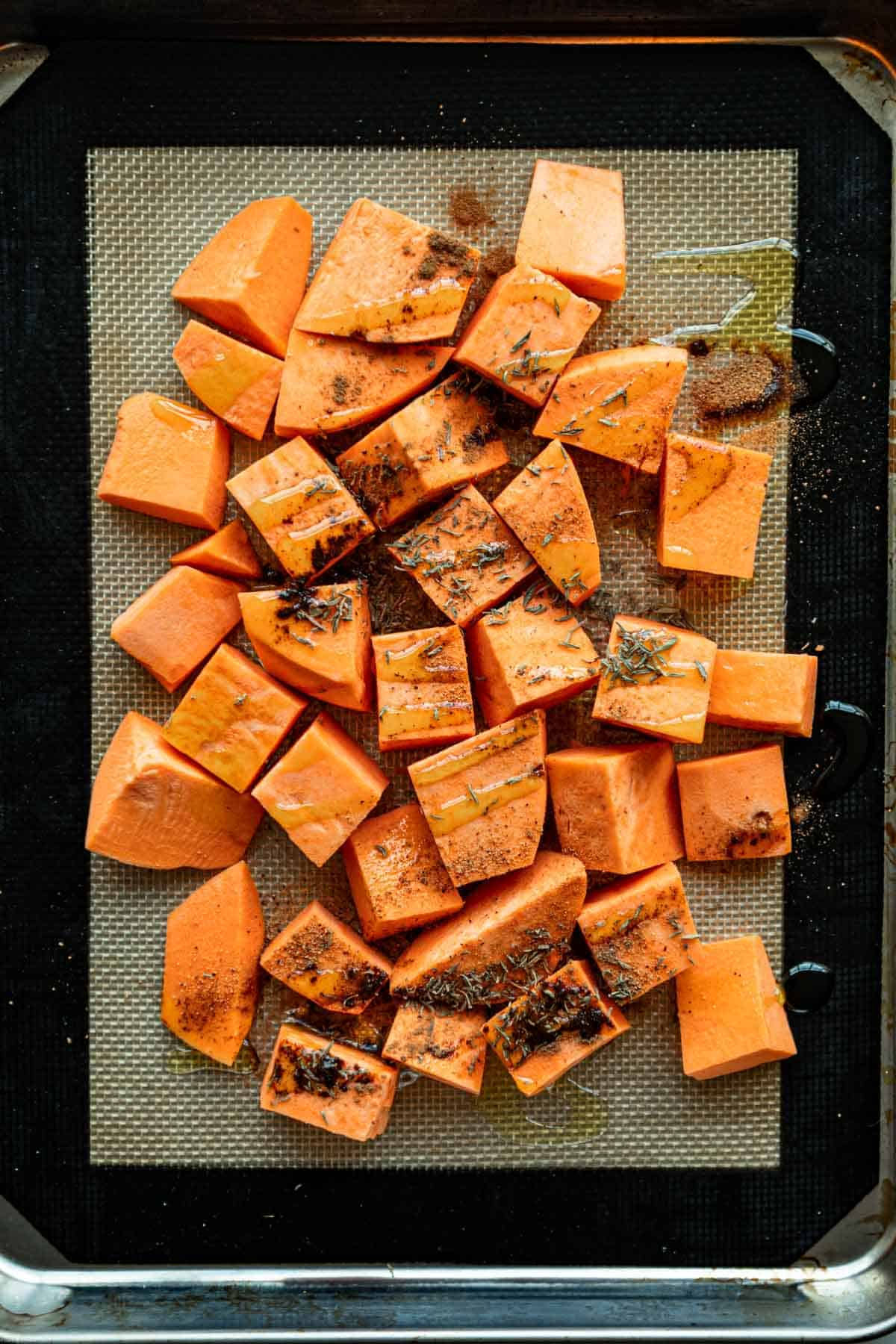 Chopped sweet potato on a baking sheet with seasonings and a drizzle of olive oil.