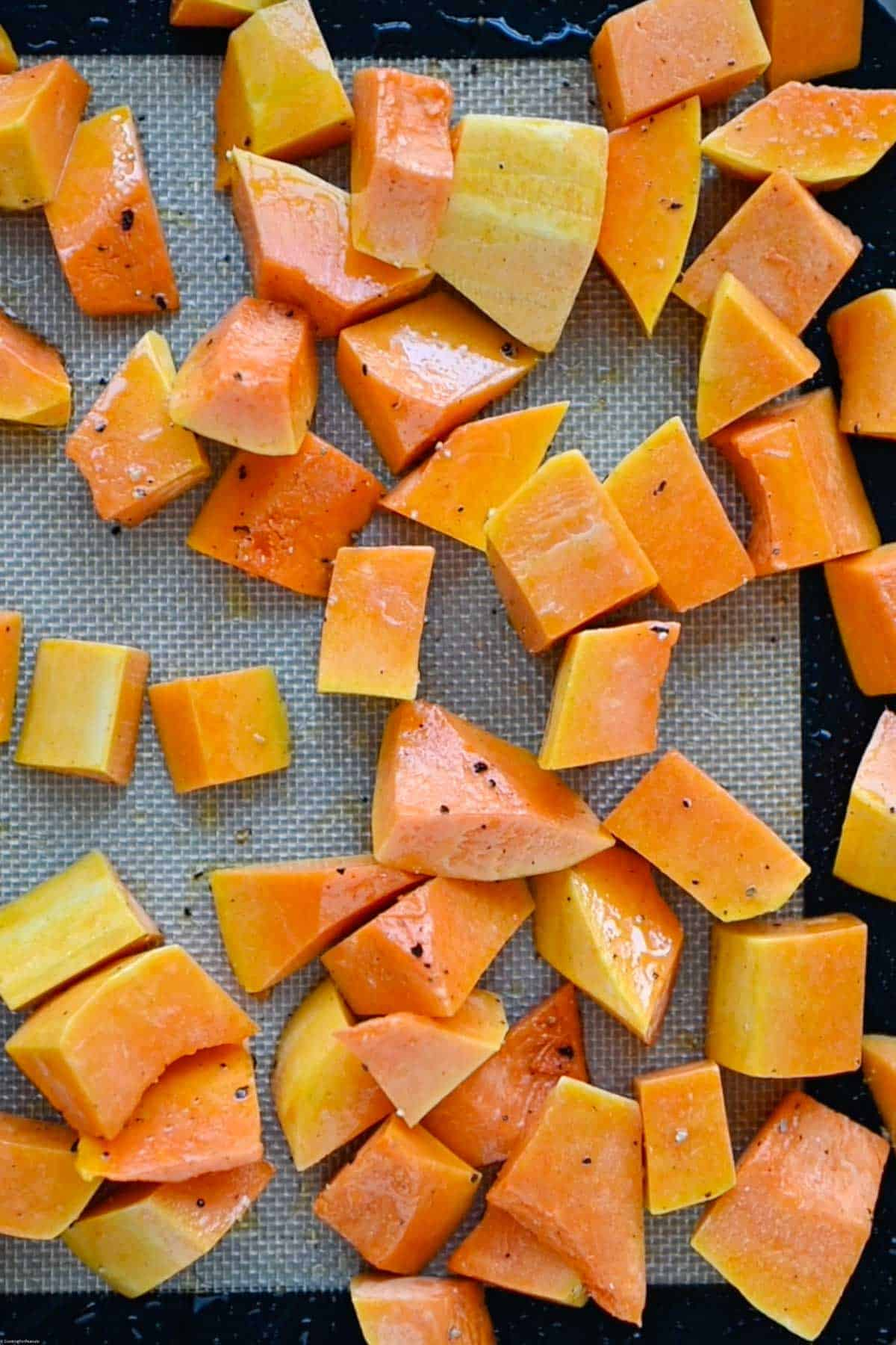 Roasted butternut squash on a rimmed baking sheet , tossed with olive oil and black pepper.