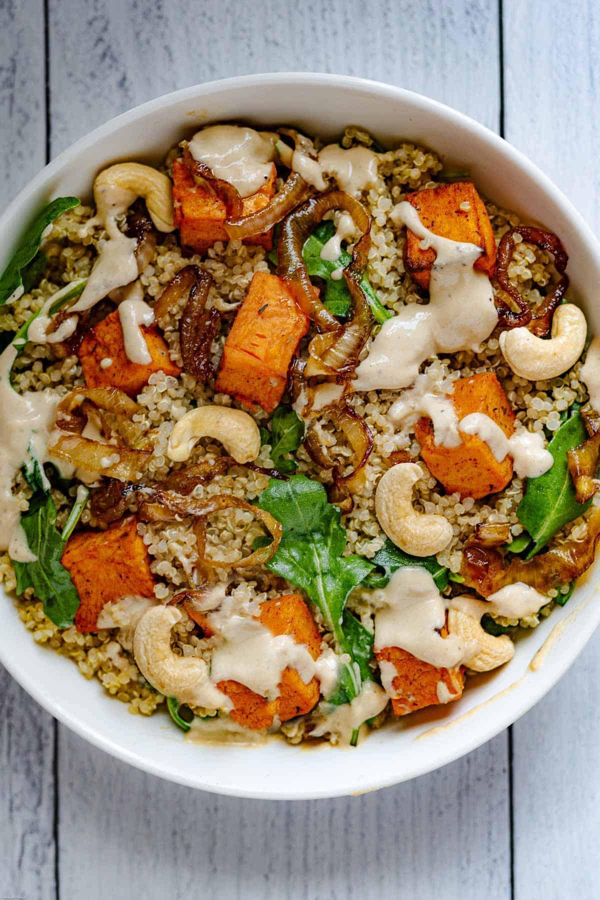 Sweet Potato & Quinoa Salad with Tahini in a white bowl.