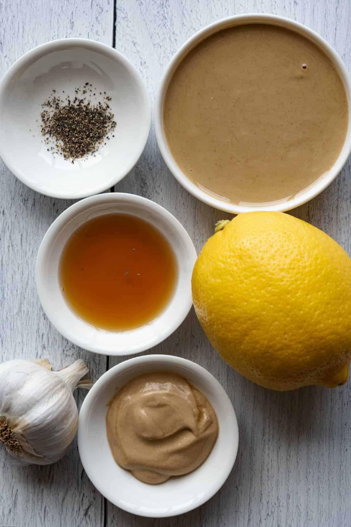 Tahini Dressing Ingredients: tahini, garlic, lemon, maple syrup, black pepper, and Dijon mustard.